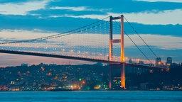 Eine türkische Flagge weht am Heck eines Schiffes über dem Bosporus. Im Hintergrund ist die Kemal-Atatürk-Brücke zu sehen, die auch Bosporus-Brücke genannt wird.