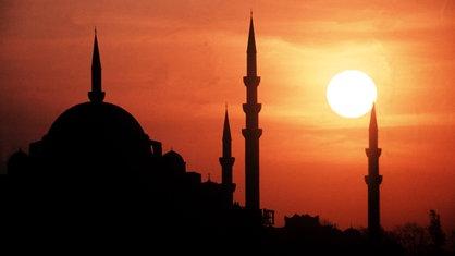 Die Sonne geht hinter den Minaretten der Suleiman-Moschee in Istanbul unter.