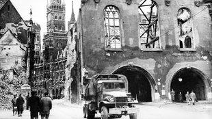 München nach Bombenangriffen im Zweiten Weltkrieg. Häuser und Kirchen sind stark beschädigt. Dächer, Wände und Fenster fehlen.
