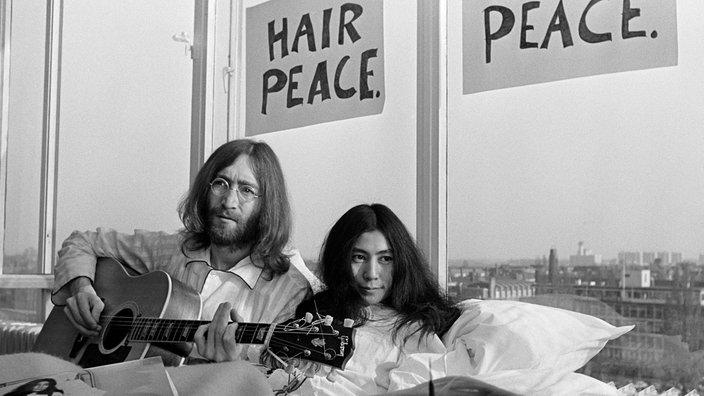 """John Lennon y Yoko Ono están sentados en una cama con dos carteles encima de ellos. """"Paz Cabello"""" y """"Cama de la paz"""""""