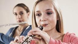 Zwei Teenager spielen auf Blasinstrumenten.