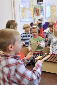 Zwei blonde Schülerinnen der zweiten Klasse spielen im Musikunterricht auf der Blockflöte.