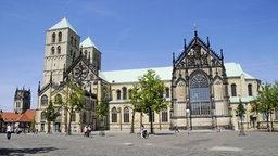 Der Dom von Münster fällt auf durch seine helle Sandsteinfarbe und die grüne Bedachung. Das Foto zeigt den Dom in seitlicher Ansicht mit seinen beiden Türmen zur Linken sowie dem langen Kirchenschiff.