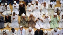 ne Gruppe von indischen Männer sitzt auf Teppichen, ins Gebet versunken.