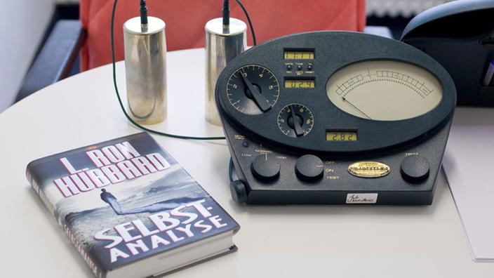 ein e meter steht auf einem tisch daneben liegt ein buch mit dem titel - L Ron Hubbard Lebenslauf