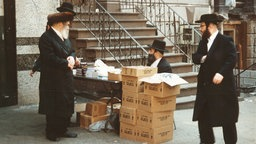 Some Orthodox Jews with beards, hats and dressed in black, standing in front of a residential building on the sidewalk. Another sitting at a table, which is also on the sidewalk.