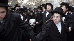 Several Orthodox Jews in black clothes, wearing hats and beards. Some of them carry a corpse, which is wrapped in a white cloth.