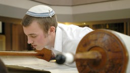 A boy wearing a kippah on his head leaning over a Torah scroll and read.