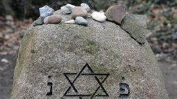 Auf einem alten Grabstein mit Davidstern liegen mehrere kleinere Steine.