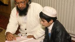 Imam liest mit einem Schüler im Koran.