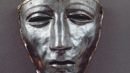 Auf dem Bild ist eine silberne Maske zu sehen die das Gesicht eines Mannes zeigt.