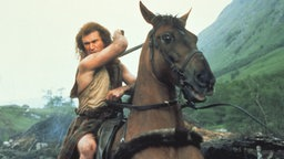 Mel Gibson als schottischer Nationalheld William Wallace in blauer Kriegsbemalung inmitten seiner Krieger in dem Film 'Braveheart'.