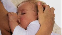 Eine Frau stillt ihr Baby.