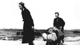 Zwei Frauen ziehen im April 1945 einen Handkarren über Land.