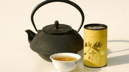 Dose mit grünem Tee, Teekanne und Schale mit grünem Tee