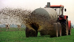 Ein Landwirt bringt auf seinem Feld Gülle aus