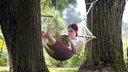 Eine Frau liegt in einer Hängematte, die zwischen zwei Bäumen gespannt ist.
