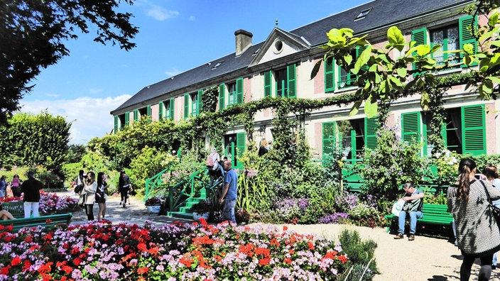 In Einem Dicht Bewachsenen Garten Steht Ein Wohnhaus Mit Spitzdach. Auch  Das Haus Ist Mit