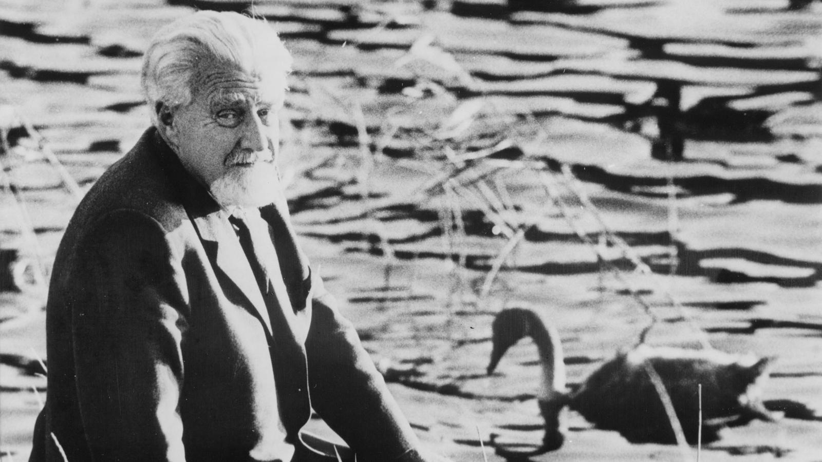 Konrad Lorenz sitzt am Wasserrand und dreht sich in Richtung Kamera, im Hintergrund schwimmt eine Ente und ein Schwan