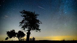 Ein Meteor verglüht am Nachthimmel.