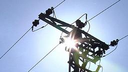 Aufnahme eines Strommastes hinter dem die Sonne am blauen Himmel steht.