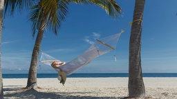 Eine Frau liegt am Strand unter Palmen in der Hängematte