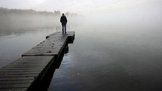 Ein Mann steht einsam am Ende eines Bootsstegs und schaut auf den Nebel am See.