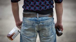 Ein Jugendlicher steht mit Schnapsflasche in der linken und Bierflasche in der rechten Hand mit dem Rücken zur Kamera