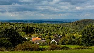Landschaft mit Wiesen, Wäldern und bewölktem Himmel in der Eifel