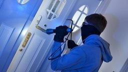 Ein Einbrecher macht sich an einer Tür zu schaffen