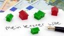 """Füller und Blatt Papier mit der Aufschrift """"Mein letzter Wille"""". Darauf liegen Monopoly-Häuser, darunter Geld."""