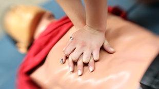 Zwei Hände üben an einer Puppe die Herzdruck-Massage