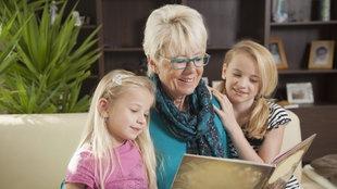 Ein Großmutter liest ihren beiden Enkelinnen ein Buch vor