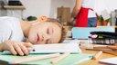 Ein Junge liegt erschöpft auf seinen Schulheften