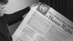 """schwarz-weiß Aufnahme einer älteren Frau, die eine Zeitung mit der Überschrift """"Human Rights"""" in der Hand hält.; Rechte: imago"""