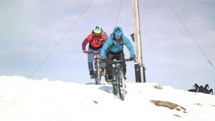 Zwei Personen fahren bei Schnee Fahrrad.