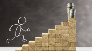 Aufgezeichnetes Tafelmännchen steigt auf eine Treppe aus Holzsteinchen, auf der am Ende Geld liegt.