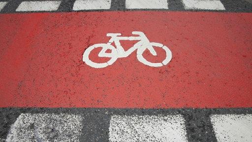 Fahrradpiktogramm auf rot gefärbtem Fahrradweg