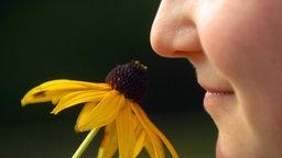 Eine Frau riecht an einer gelben Blume