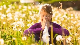 Mädchen sitzt auf einer Wiese und putzt sich die Nase mit einem Taschentuch.