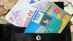 Bankkarten und Geldscheine schauen aus einer Geldbörse heraus. Im Hintergrund liegen Münzen auf einem Tisch