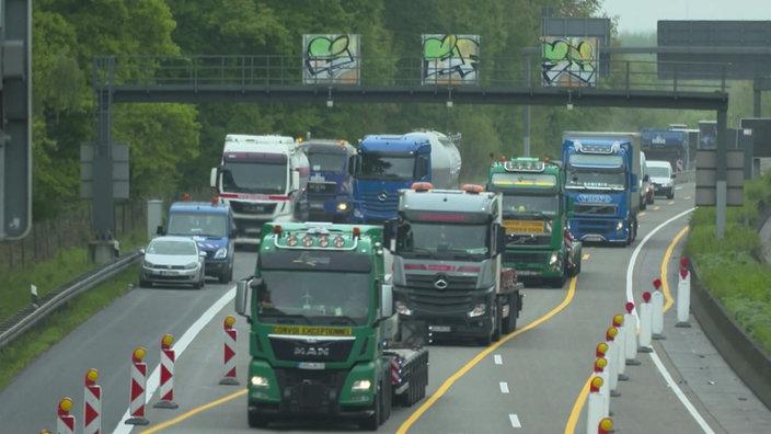 Camiones en línea en la carretera cuando el carril se está estrechando debido a trabajos de construcción.