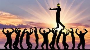 Stilisierte Darstellung: Ein Mann mit Krone auf dem Kopf läuft auf den Händen von anderen Personen, während er von der Sonne angestrahlt wird