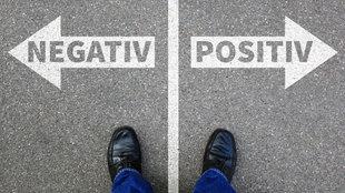 Auf dem Boden zwei Pfeile mit der Aufschrift 'positiv' und 'negativ'.