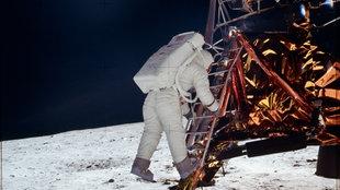 Ein Astronaut im Anzug klettert auf einer Leiter von seiner Raumkaspel auf die Mondoberfläche.