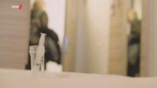 Eine Spritze mit Sperma steht in einem Glas auf dem Tisch