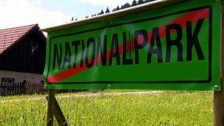 """Durchgestrichenes Schild mit Beschriftung """"Nationalpark"""" auf einer Wiese."""
