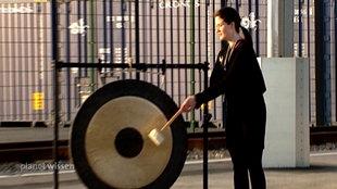 Eine Frau in schwarzer Kleidung spielt einen großen Gong mit dem Gongschlägel.