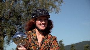 Frau mit Fahrradhelm und Pokal