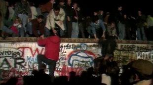 Menschenmenge an und auf der Berliner Mauer